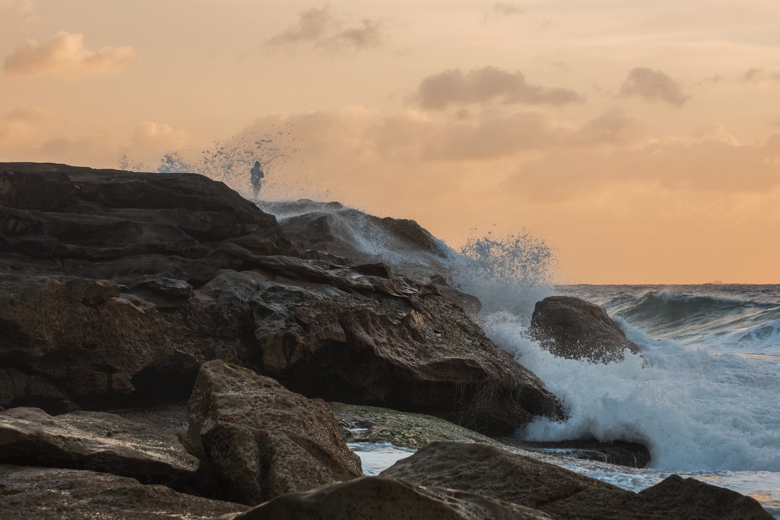 Rock fishing on the cliff with big waves